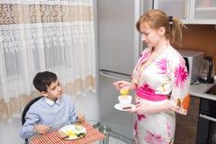年轻愉快的美丽的吃健康早餐的母亲和她的孩子 免版税库存照片
