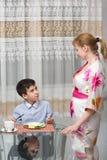 年轻愉快的美丽的吃健康早餐的母亲和她的孩子 图库摄影