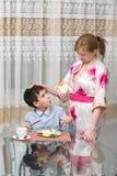 年轻愉快的美丽的吃健康早餐的母亲和她的孩子 免版税图库摄影