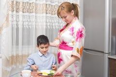 年轻愉快的美丽的吃健康早餐的母亲和她的孩子 库存照片