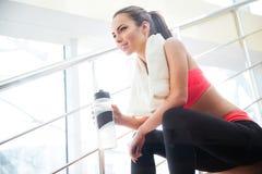 愉快的美丽的在台阶的女运动员饮用水在健身房 库存图片