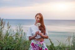 愉快的美丽的在天空和海背景的妇女吹的蒲公英,获得乐趣和演奏享受自然, su的室外,青少年的女孩 免版税库存图片