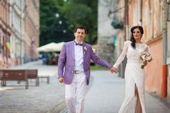 愉快的美丽的夫妇、握在stree的新娘和新郎手 免版税库存照片