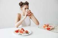 愉快的美丽的女孩微笑的坐在喝健康在白色墙壁的桌上戒毒所新鲜的葡萄柚圆滑的人 库存照片