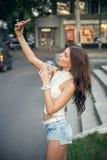 愉快的美丽的女孩饮用的冰冻咖啡和采取在电话的一selfie 库存图片