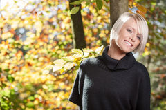 愉快的美丽的妇女在秋天森林 免版税库存照片