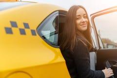 愉快的美丽的妇女在黄色出租汽车坐 库存照片