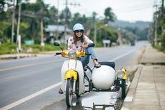 愉快的美丽的妇女坐摩托车 库存图片