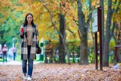 愉快的美丽的妇女饮用的咖啡在秋天 免版税库存图片