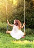 愉快的美丽的小女孩坐跷跷板夏日, bac 免版税库存照片
