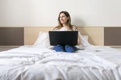 愉快的美丽的少妇在家坐床使用膝上型计算机 免版税库存图片