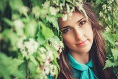 愉快的美丽的少妇在春天开花公园 免版税库存图片