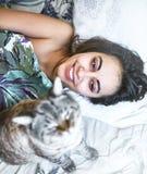 愉快的美丽的少妇早晨在床上与猫 库存照片