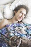 愉快的美丽的少妇早晨在床上与猫 免版税图库摄影