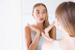 愉快的美丽的年轻女人,当看镜子时 在她的皮肤的麻烦,秀丽概念 免版税库存图片