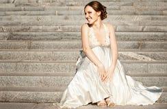愉快的美丽的新娘坐台阶 库存照片