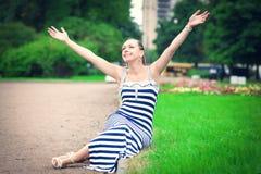 愉快的美丽的时髦的女人坐草坪 库存图片