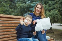 愉快的美丽的母亲和儿子吃棉花糖 免版税库存照片
