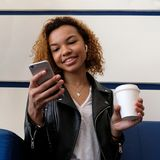 愉快的美丽的深色皮肤的女孩调查电话,当坐一个蓝色沙发在候诊室或在咖啡馆时 一wirel 免版税库存图片