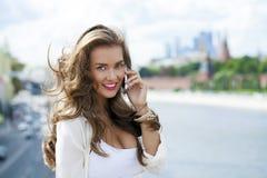 愉快的美丽的白肤金发的女孩叫由在夏天街道的电话 免版税库存图片
