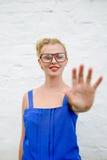 愉快的美丽的白肤金发的女孩画象用在感人的移动的手,在白色背景特写镜头 免版税库存图片