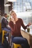 愉快的美丽的白肤金发的妇女谈话在celllphone在咖啡店 库存照片