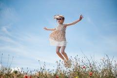 愉快的美丽的跳跃小女孩佩带的太阳镜和的礼服户外 免版税库存图片