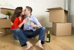 愉快的美国夫妇坐打开一起庆祝用香槟多士的地板移动在一个新房里 免版税库存图片