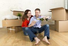 愉快的美国夫妇坐打开一起庆祝用香槟多士的地板移动在一个新房里 库存图片