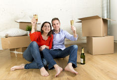 愉快的美国夫妇坐打开一起庆祝用香槟多士的地板移动在一个新房里 库存照片