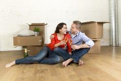 愉快的美国夫妇坐打开一起庆祝用香槟多士的地板移动在一个新房里 免版税图库摄影