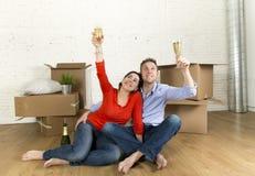 愉快的美国夫妇坐打开一起庆祝用香槟多士的地板移动在一个新房里 免版税库存照片