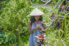愉快的美国黑人的黑人妇女30s探索的米在戴农村传统亚洲帽子的巴厘岛调遣森林和密林使用mobi 免版税库存图片