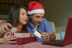 愉快的美好的加上可爱的亚裔中国妇女和白丈夫在圣诞老人圣诞节帽子使用信用卡和膝上型计算机c 库存图片