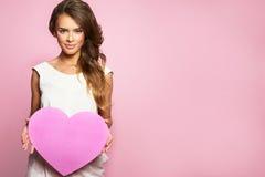 年轻愉快的美好的妇女举行爱标志红色心脏 隔绝在演播室桃红色背景女性模型 图库摄影