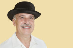 愉快的老人佩带的帽子,当查寻在黄色背景时 免版税库存照片