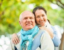 愉快的老人和成熟妇女反对森林 免版税库存照片