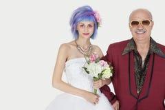 愉快的老人常设胳膊画象在胳膊的有婚礼礼服的美丽的女儿的反对灰色背景 免版税库存照片