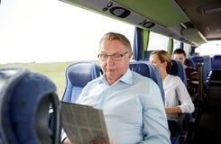 愉快的老人读书报纸在旅行公共汽车上 免版税图库摄影