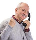 愉快的老人画象谈话在老输送路线电话 免版税库存图片