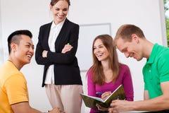 愉快的老师和她的学生 库存照片