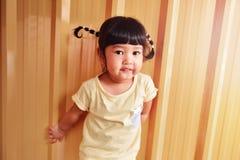 愉快的聪明的孩子画象,有一点微笑的亚裔女孩在她 免版税图库摄影