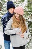 愉快的肉欲的夫妇在冷杉木中的森林里在雪 免版税图库摄影