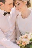 愉快的肉欲的英俊的新郎和白肤金发的美丽的新娘拥抱白色的礼服的,特写镜头 免版税库存图片