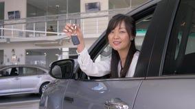 愉快的自动购买,亚洲妇女客户喜悦与坐在沙龙和偷看通过窗口的新的购买和展示钥匙 股票录像