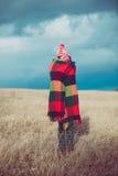 愉快的自由的妇女无忧无虑在秋天或冬天在享用太阳的一条温暖的毯子下 库存图片