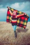 愉快的自由的妇女无忧无虑在秋天或冬天在享用太阳的一条温暖的毯子下 免版税图库摄影