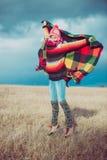 愉快的自由的妇女无忧无虑在秋天或冬天在享用太阳的一条温暖的毯子下 免版税库存图片