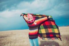 愉快的自由的妇女无忧无虑在秋天或冬天在享用太阳的一条温暖的毯子下 库存照片