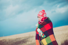 愉快的自由的妇女无忧无虑在秋天或冬天在享用太阳的一条温暖的毯子下 免版税库存照片